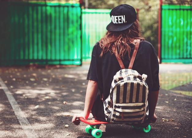 Junges mädchen, das auf kunststoff orange penny shortboard auf asphalt in kappe sitzt