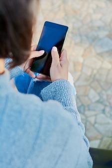 Junges mädchen, das auf smartphone spricht und mitteilungen mit smartphone schreibt