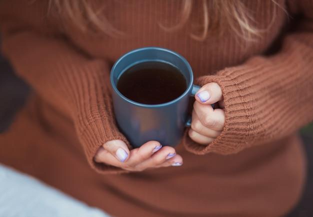 Junges mädchen, das becher heißen kaffee in einer hand hält