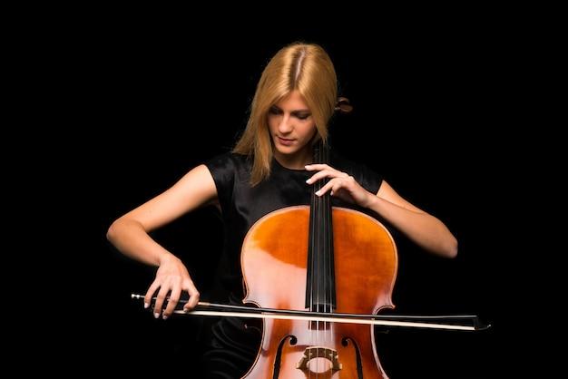 Junges mädchen, das das cello auf lokalisiertem schwarzem hintergrund spielt