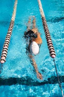 Junges mädchen, das das schwimmen am pool genießt