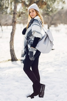 Junges mädchen, das decke auf einem schneebedeckten feld trägt