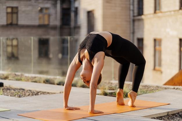Junges mädchen, das dehnungs- und yoga-trainingsübung übt
