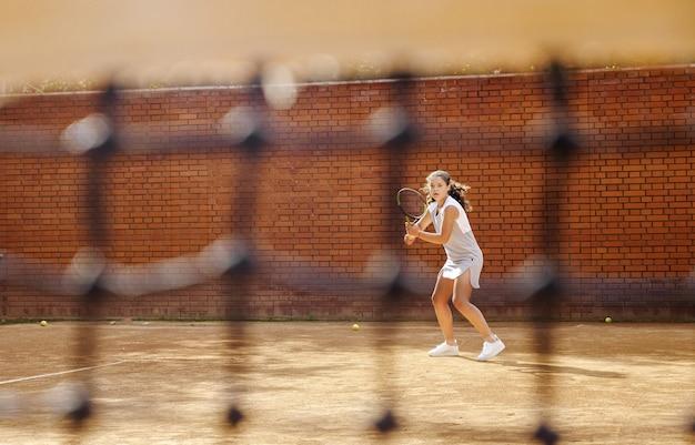 Junges mädchen, das den ball mit dem tennisschläger während des trainings blockiert