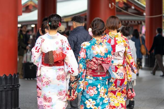 Junges mädchen, das den japanischen kimono steht vor sensoji-tempel in tokyo, japan trägt.