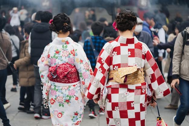 Junges mädchen, das den japanischen kimono steht vor sensoji-tempel trägt