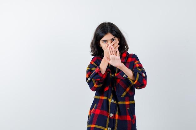 Junges mädchen, das den mund mit der hand bedeckt, während es ein stoppschild in einem karierten hemd zeigt und ernst aussieht, vorderansicht.
