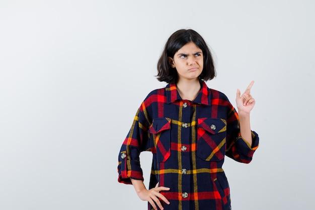 Junges mädchen, das den zeigefinger in der heureka-geste anhebt, während es die hand in kariertem hemd an der taille hält und nachdenklich aussieht. vorderansicht.