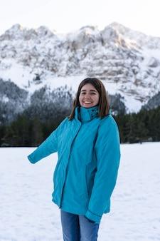 Junges mädchen, das die alpen mit den schneebedeckten bergen auf dem rücken wandert