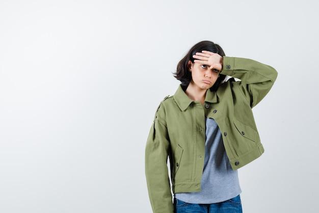 Junges mädchen, das die hand auf die stirn in grauem pullover, khakijacke, jeanshose legt und müde aussieht, vorderansicht.