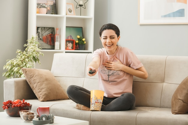 Junges mädchen, das die tv-fernbedienung zur kamera hält, die auf dem sofa hinter dem couchtisch im wohnzimmer sitzt?