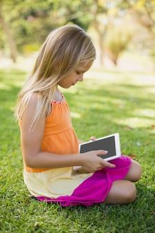 Junges mädchen, das digitale tablette im park verwendet