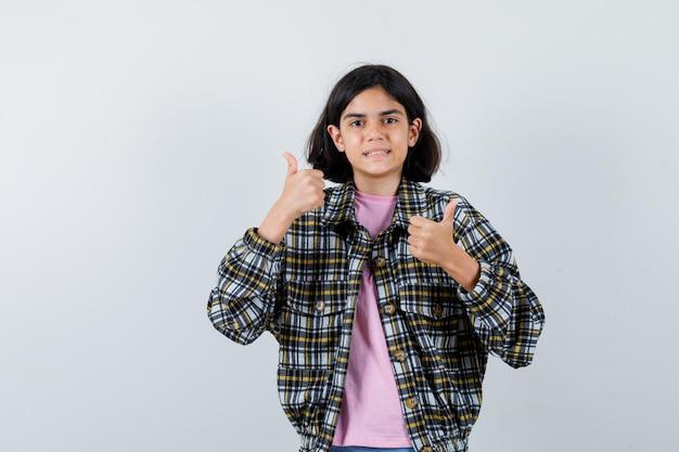 Junges mädchen, das doppelte daumen hoch in kariertem hemd und rosa t-shirt zeigt und glücklich aussieht, vorderansicht.