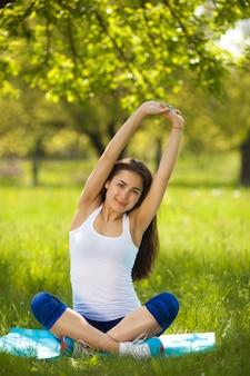 Junges mädchen, das draußen ausarbeitet. schönheit, die pilates, yoga und eignungsübungen auf natur tut.