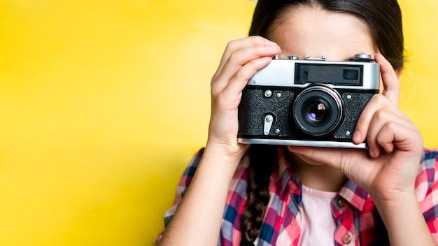 Junges mädchen, das ein bild mit einer retro-kamera macht