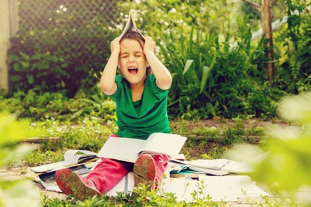 Junges mädchen, das ein buch beim lügen im gras liest.