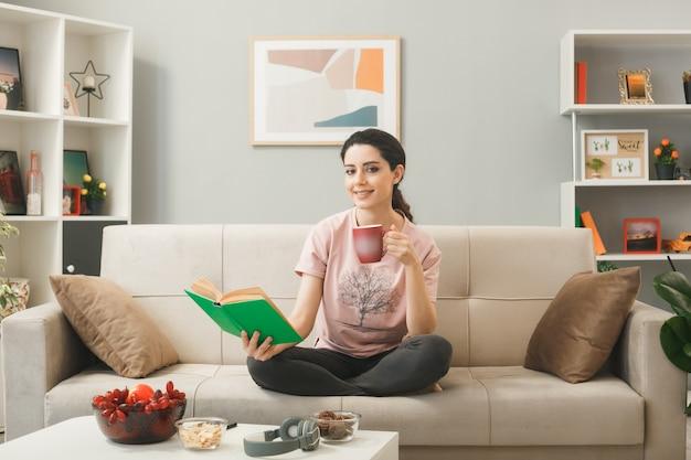 Junges mädchen, das ein buch mit einer tasse tee hält, das auf dem sofa hinter dem couchtisch im wohnzimmer sitzt?