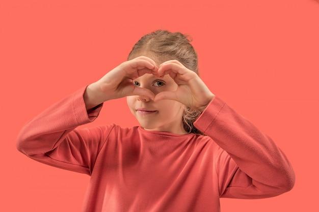 Junges mädchen, das ein herz mit ihren fingern bildet