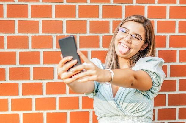Junges mädchen, das ein selfie macht - lächeln in die kamera - glückliche schülerin, die an der wand steht und ihr smartphone benutzt