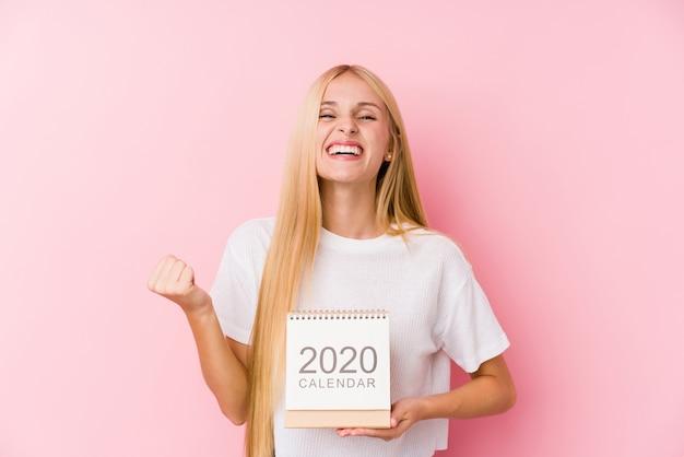 Junges mädchen, das ein zujubeln des kalenders 2020 sorglos und aufgeregt hält.