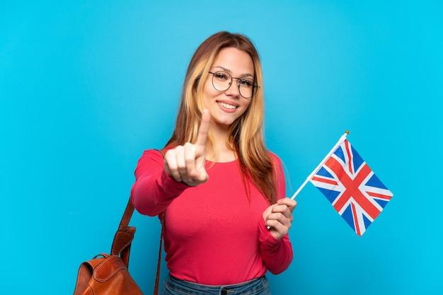 Junges mädchen, das eine britische flagge über isolierter blauer wand hält, die einen finger zeigt und hebt