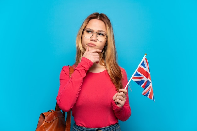 Junges mädchen, das eine britische flagge über isolierter blauer wand hält, die zweifel hat