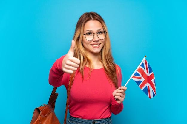 Junges mädchen, das eine britische flagge über isolierter blauer wand mit daumen hoch hält, weil etwas gutes passiert ist