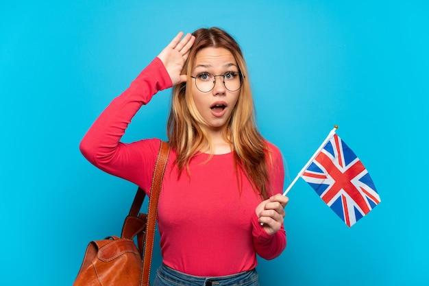 Junges mädchen, das eine britische flagge über isolierter blauer wand mit überraschungsausdruck hält