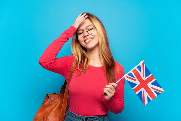 Junges mädchen, das eine flagge großbritanniens über isolierter blauer wand hält, die viel lächelt