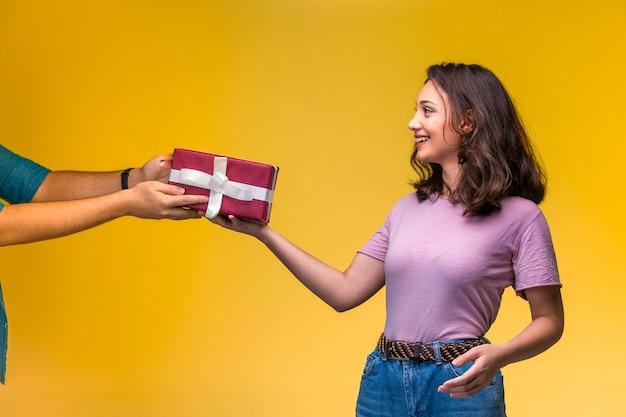 Junges mädchen, das eine geschenkbox von ihrem freund an ihrem jahrestag nimmt und glücklich aussieht.