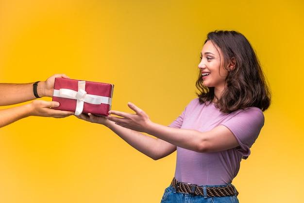 Junges mädchen, das eine geschenkbox von ihrem freund an ihrem jahrestag nimmt