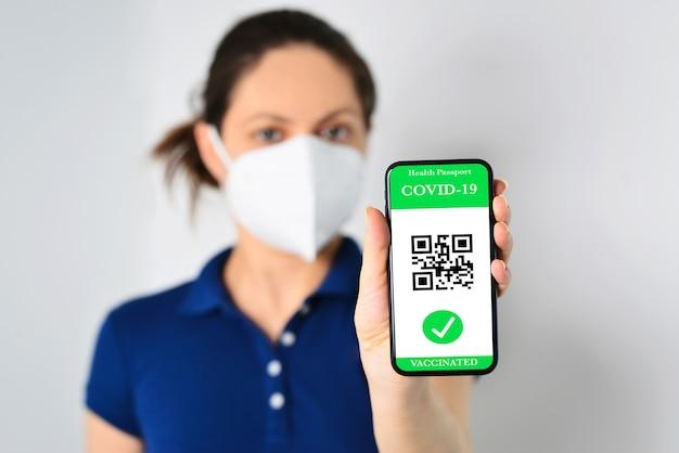 Junges mädchen, das eine gesichtsmaske trägt und ein smartphone mit grünem pass hält
