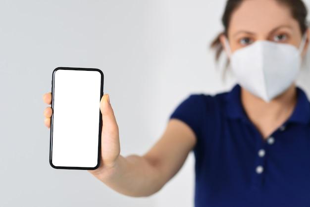 Junges mädchen, das eine gesichtsmaske trägt und ein smartphone mit weißem bildschirm hält