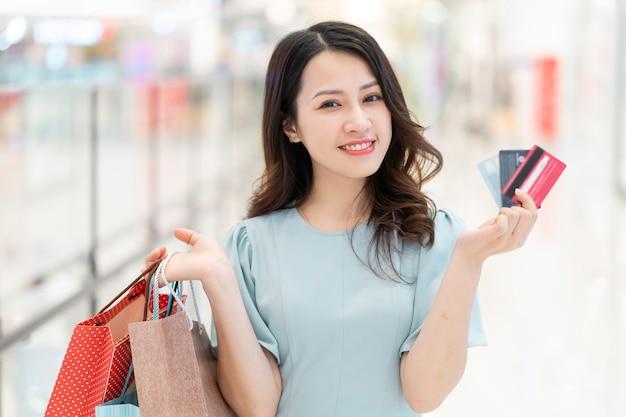 Junges mädchen, das eine kreditkarte im einkaufszentrum hält