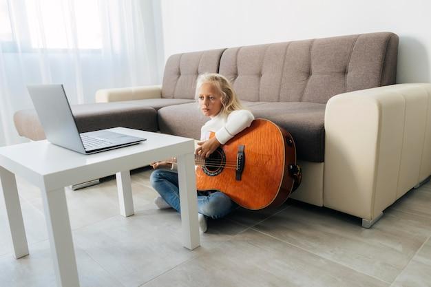 Junges mädchen, das eine online-gitarrenstunde nimmt
