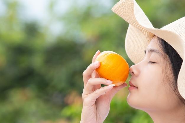 Junges mädchen, das eine orange frucht in ihrer hand hält und sie riecht