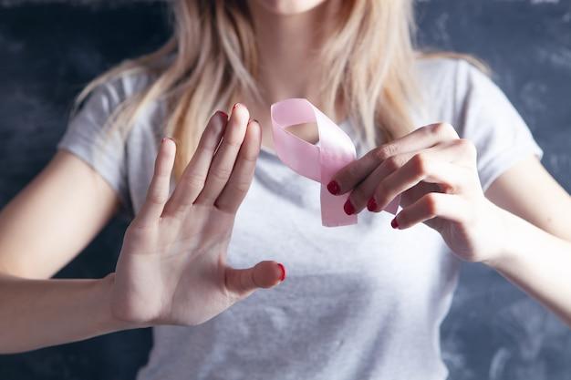 Junges mädchen, das eine rosa schleife hält und halt zeigt