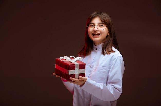 Junges mädchen, das eine rote geschenkbox hält und betrachtet.