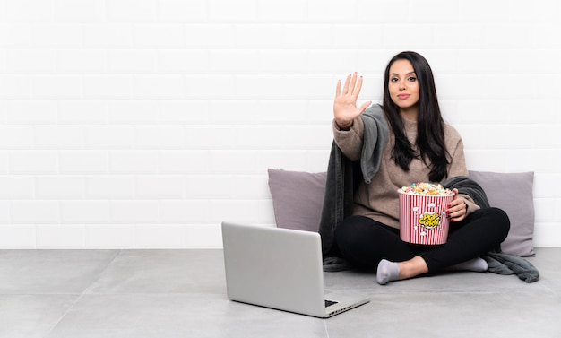 Junges mädchen, das eine schüssel popcorn hält und einen film in einem laptop zeigt, der stoppgeste macht