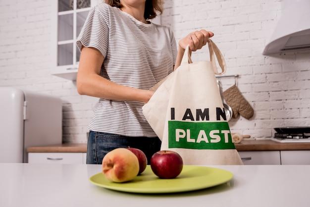 Junges mädchen, das eine stofftasche hält. in der küche. ich bin kein plastik.