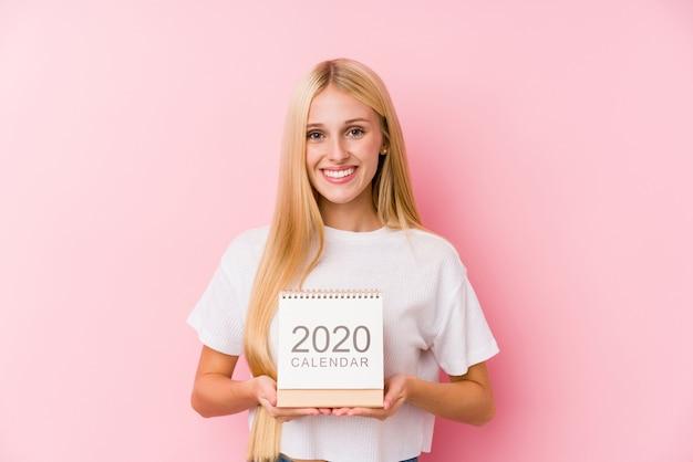 Junges mädchen, das einen kalender 2020 glücklich, lächelnd und fröhlich hält.
