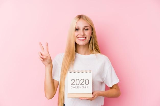 Junges mädchen, das einen kalender 2020 hält, der nummer zwei mit den fingern zeigt.