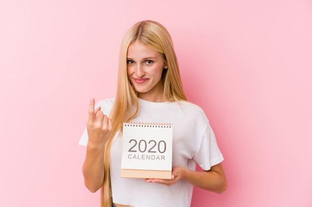 Junges mädchen, das einen kalender 2020 zeigt mit dem finger auf sie hält, als ob einladung näher kommen.