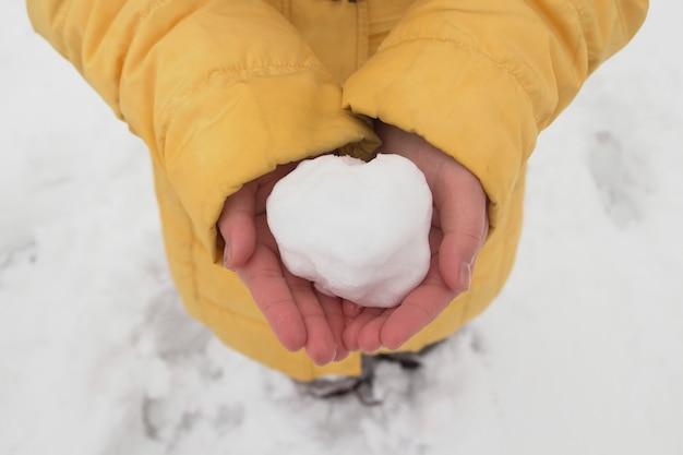 Junges mädchen, das einen schneeball in ihren händen im winterpark hält
