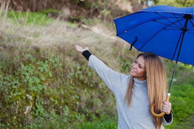 Junges mädchen, das einen spaziergang mit einem blauen regenschirm macht