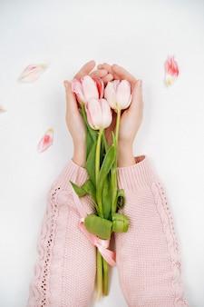 Junges mädchen, das einen strauß rosa tulpen hält. ansicht von oben, weißer hintergrund, textkopierraum.