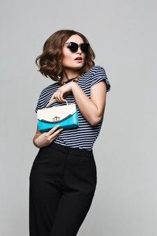 Junges mädchen, das emotion tut. gekleidet in ein gestreiftes hemd, schwarze hosen, sonnenbrille und helle lippen, modekleidung. tragen von vintage-sonnenbrille, ausrüstung, freizeitstil, helle frauenfarben. sinnlich