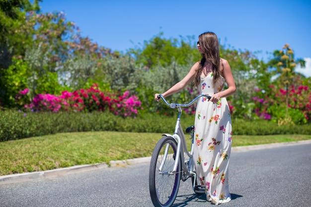 Junges mädchen, das fahrrad auf tropisches erholungsort fährt