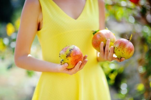 Junges mädchen, das frische reife granatäpfel im sonnigen garten in italien auswählt. weiblicher landwirt, der im obstgarten arbeitet