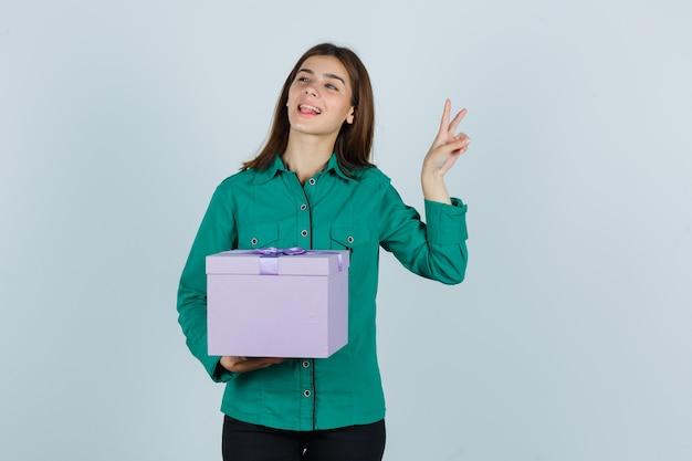 Junges mädchen, das geschenkbox hält, friedensgeste in der grünen bluse, in der schwarzen hose zeigt und fröhlich schaut, vorderansicht.